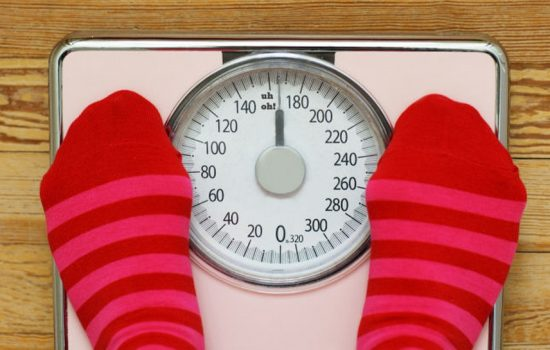 Persona standing on a set of scales | Moving Minds Hypnotherapy
