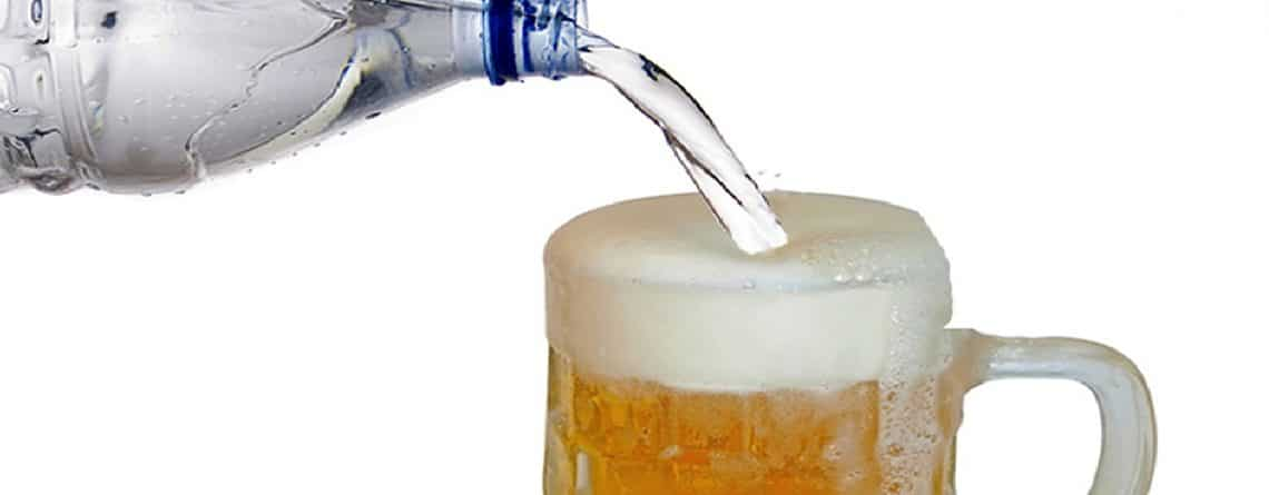water poured into glass with beer in it