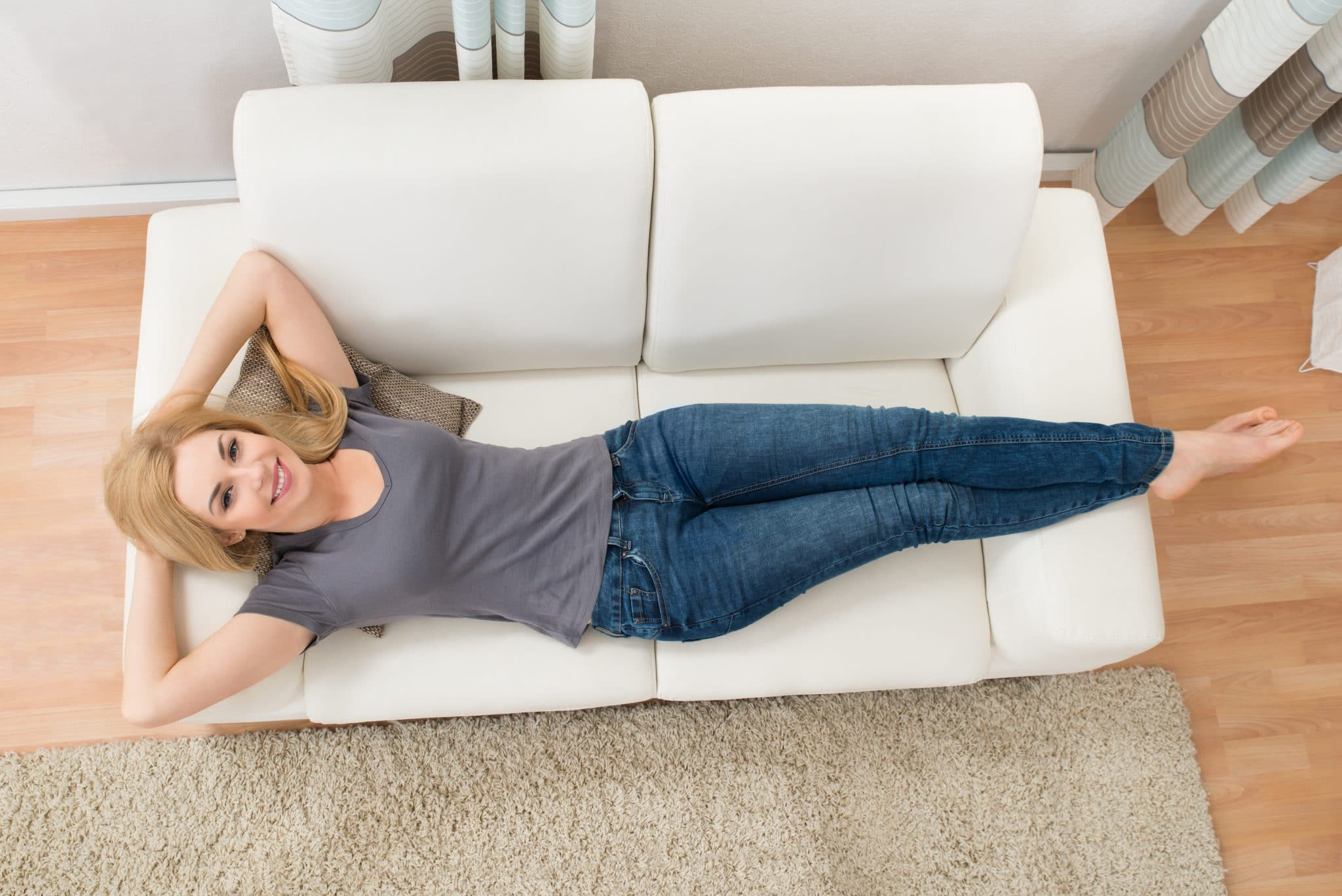 Happy woman lying on white sofa | Moving Minds Hypnotherapy