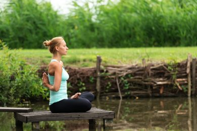 Woman meditating beside a lake | Moving Minds Hypnotherapy