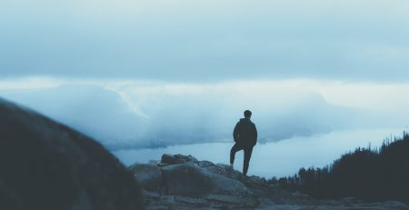 Man standing on a cliff | Moving Minds Hypnotherapy