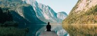 Man sitting on a wharf at a lake | Moving Minds Hypnotherapy