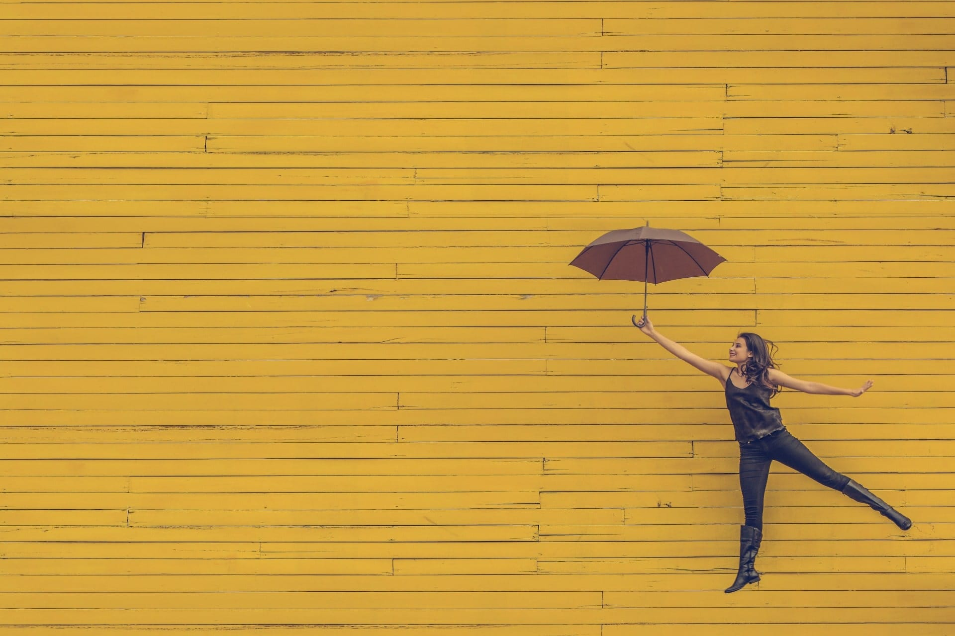 Woman jumping with an umbrella | Moving Minds Hypnotherapy