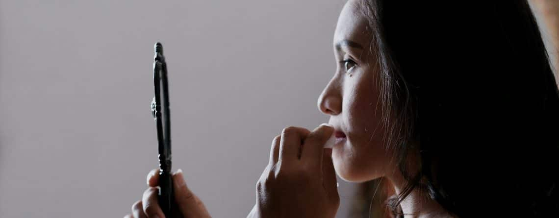 Woman looking in a mirror | Moving Minds Hypnotherapy